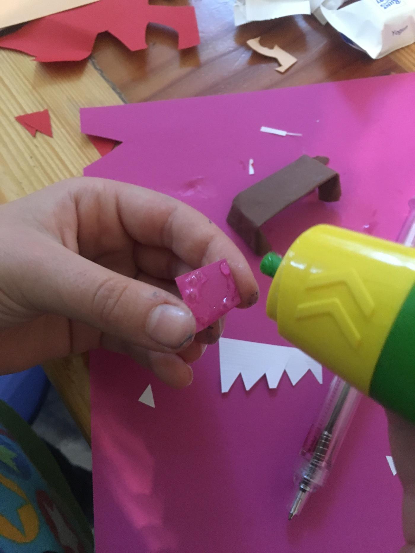 Kind trägt Kleber auf Papier auf