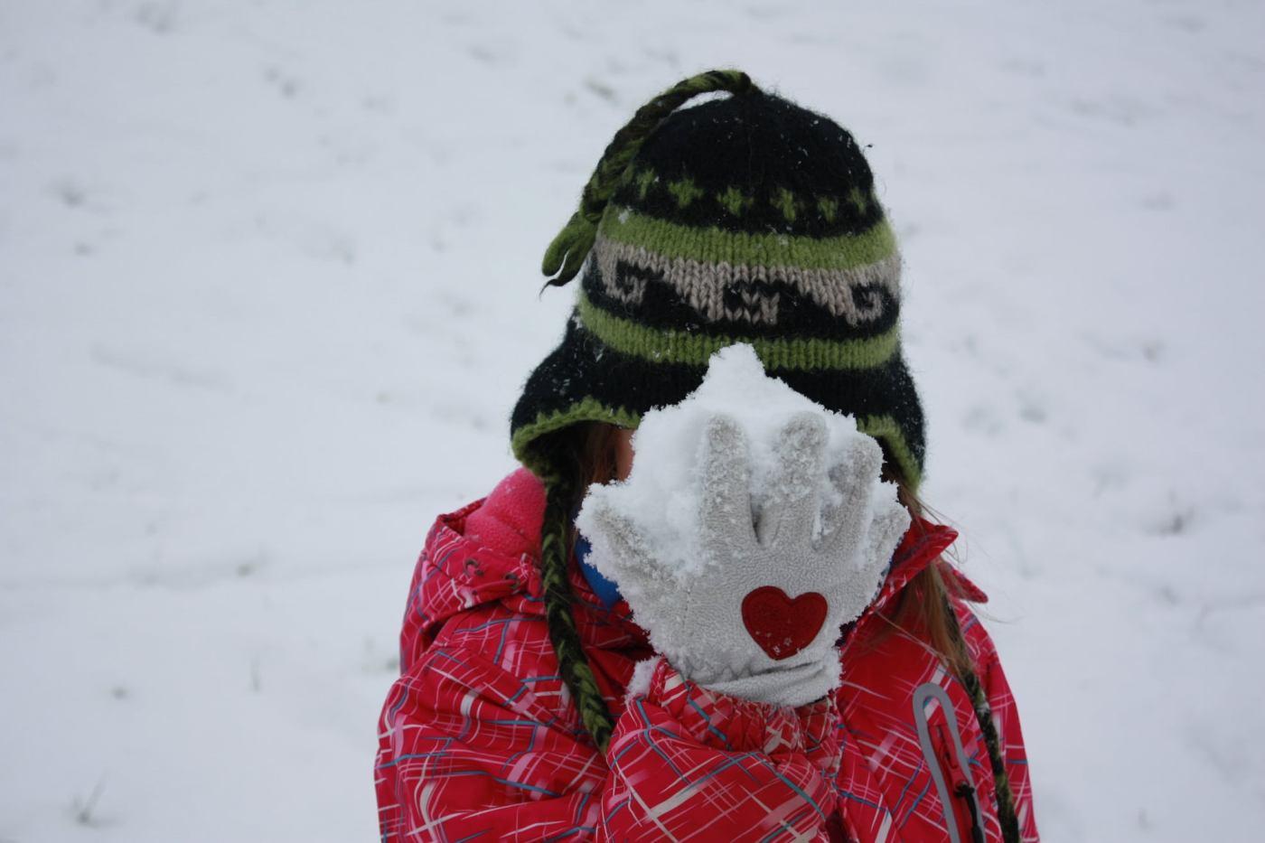 Kind mit einer Hand voll Schnee vorm Gesicht
