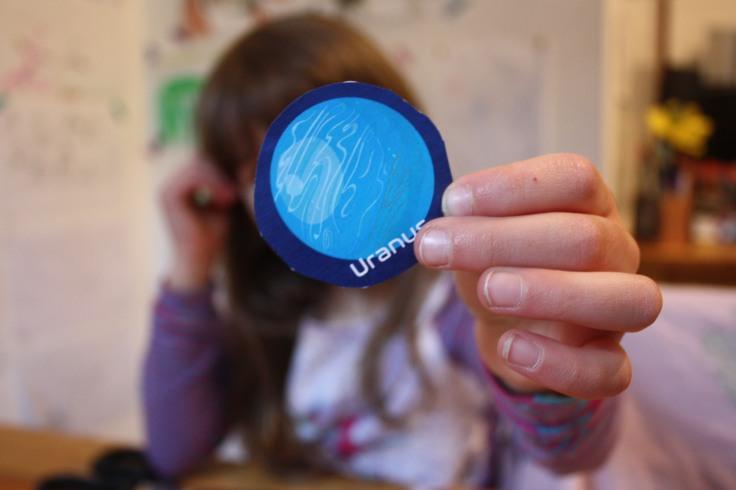 Kind hält Uranus aus Papier
